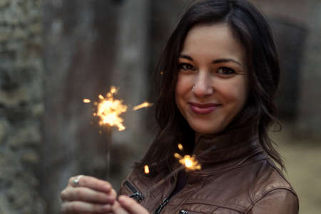 portrait of a beautiful young woman holding little lights Stock Photo - 99650259