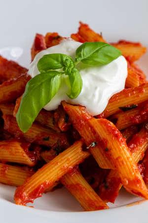 fresh penne arrabiata pasta in white plate