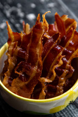 fresh tasty crispy bacon strips in a bowl