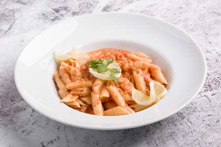 tasty penne with tuna pasta on white plate