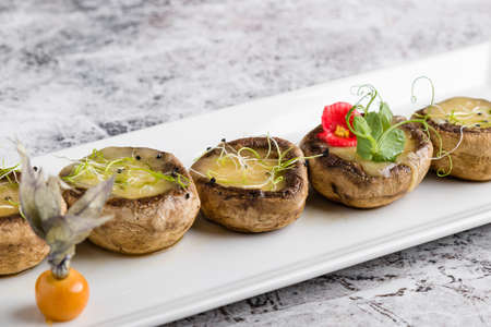 grilled mushroom stuffed with cheese on white plate