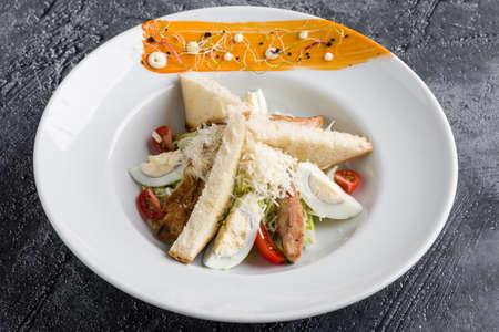 fresh tasty caesar salad appetizer in white plate