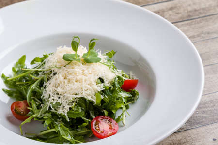fresh tasty healthy rucola salad in white plate
