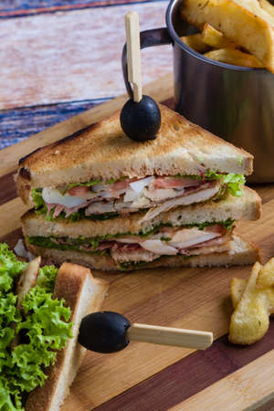 tasty chicken club sandwich with fries on wooden table