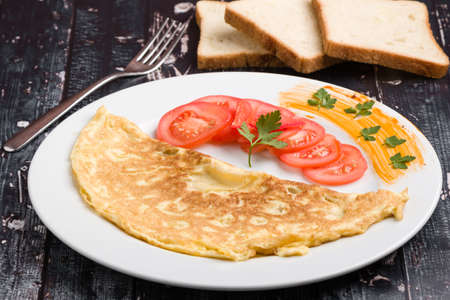 filled omelette with cheese and tomato on white plate