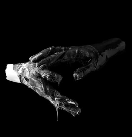 concept image of two hands covered in black and white paint touching