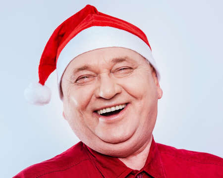 laughing out loud: Close up portrait of laughing out loud middle aged man with red Santa Claus hat and shirt over white background