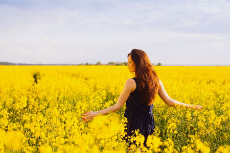 Young woman in sleeveless dress enjoying sunlight and nature on yellow blooming rapeseed field Stock Photo