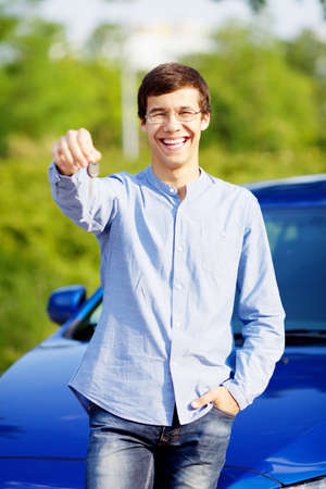 Happy young man in glasses standing in front of his new car and showing car key photo