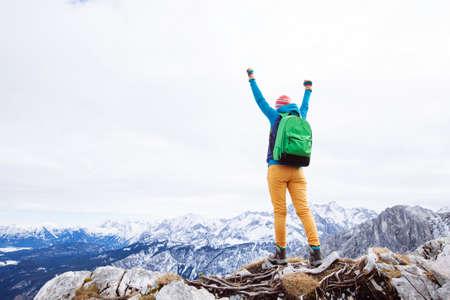 Feiern: Weibliche Wanderer mit Rucksack hob die Hände feiert erfolgreichen Aufstieg zum Gipfel des Berges