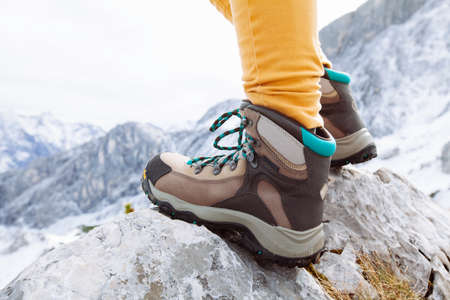 Close up of womans legs in heavy hiking boots standing on top of mountain photo