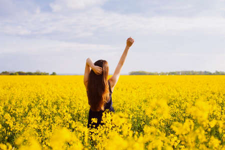 sleeveless dress: Young woman in sleeveless dress enjoying sunlight and nature on yellow blooming rapeseed field Stock Photo