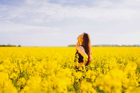 Side view of young woman with long hair touching her neck on yellow blooming rapeseed field photo