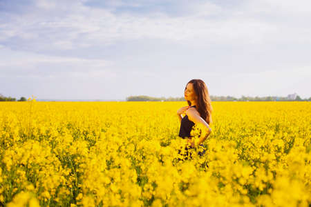 Side view of young woman with long hair touching her shoulder on yellow blooming rapeseed field photo