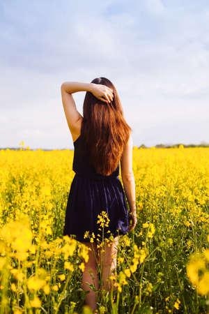 pelo largo: Vista trasera de una mujer joven con la mano en el pelo largo en campo amarillo de colza en flor