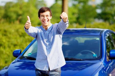 Jonge gelukkige mens in glazen die zich in de voorkant van zijn nieuwe auto en het tonen van duim omhoog en autosleutel