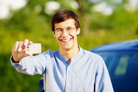 test passed: Smiling young man in glasses showing his driving license outdoor in sunny summer day