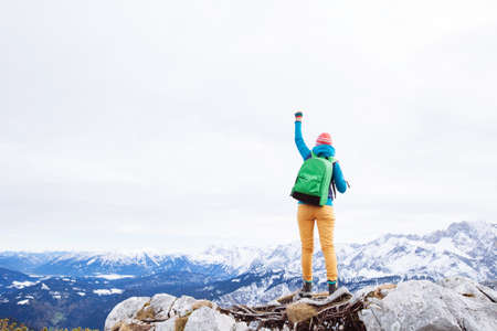 courage: Female hiker with backpack raised her hands celebrating successful climb to top of mountain