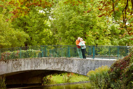 pensionary: Mature couple leaning on railing of bridge resting during stroll in park