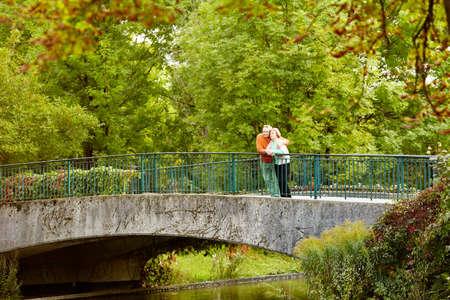 personas abrazadas: Pareja mayor apoyado en la barandilla del puente de descanso durante paseo en el parque