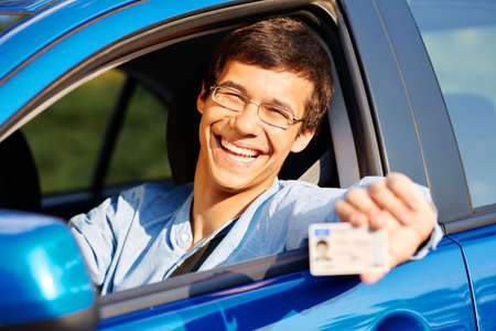 drivers license: Happy young man in glasses showing his driving license from open car window