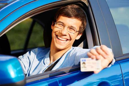 manejando: Hombre joven feliz en copas mostrando su carné de conducir desde la ventana abierta del coche Foto de archivo