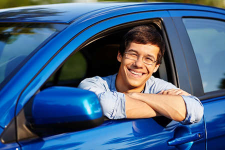 lean out: Portrait of young handsome smiling man in glasses looking out through open car window outdoor in sunny day
