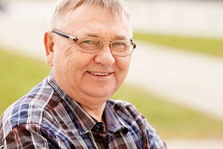 Close up outdoors portrait of smiling middle aged man in glasses and cheered shirt