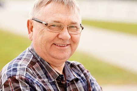 Close up im Freien Porträt der lächelnden Mann mittleren Alters mit Brille und jubelten Shirt Standard-Bild