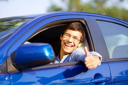 new driver: Smiling handsome young driver showing thumb up through open car window Stock Photo