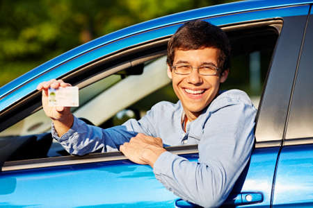 new driver: Happy young man in glasses showing his driving license from open car window