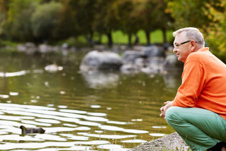 Profile of aged man in glasses sitting near pond in park watching ducks Stock Photo