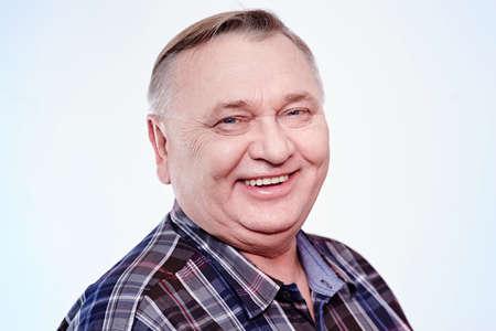 笑いの肖像画に近い白い背景の上の格子縞のシャツの男の歳