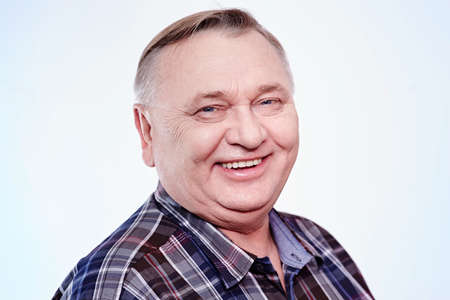 Close up portrait of laughing aged man in plaid shirt over white background