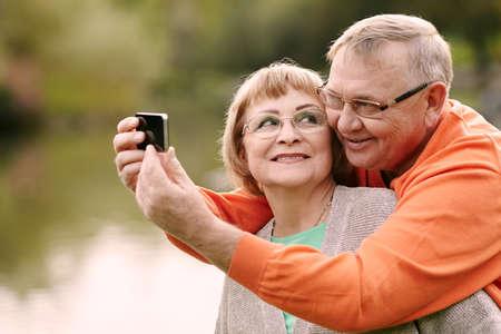 ancianos caminando: Feliz sonriente pareja de ancianos toma imagen de s� mismos con el tel�fono inteligente al aire libre