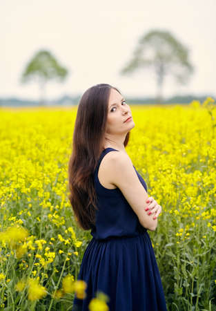 sleeveless dress: Profile of young beautiful woman with dark blue sleeveless dress and long dark hair standing on yellow blooming rapeseed field with crossed arms Stock Photo