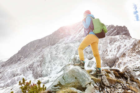 winter people: Woman hiker with backpack on top of mountain stopped on sunny mountain ledge to catch breath after long hike