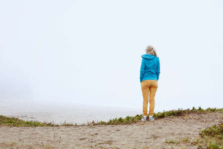 standing alone: Rear view of lonely blonde woman with hands in pockets standing on misty secluded beach on Pacific Coast