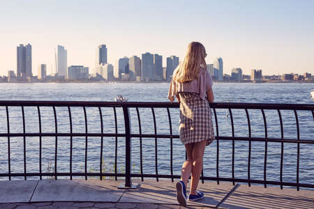 sweater girl: Back view of blonde young woman leaning on berth railing in port on sunny summer day Stock Photo