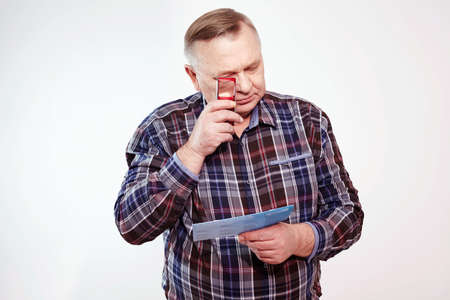 Senior man in plaid shirt reading letter with magnifying glass over white background
