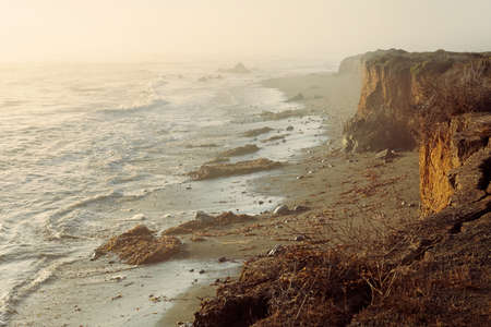 cliff edge: Sea coastal foggy sunset landscape of cliff edge with big cracks and withered plants after landslide