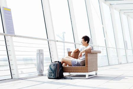 gente aeropuerto: Hombre sonriente joven en vidrios y auriculares sentado en la silla en la sala del aeropuerto de salida