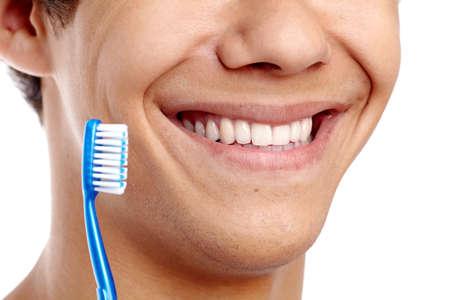 ?  ?    ?  ?    ?  ?    ?  smiling: Concepto de higiene dental con el primer plano de la sonrisa masculina con dientes sanos y azul cepillo de dientes Foto de archivo