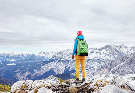 Female hiker with backpack standing on top of mountain Stock Photo
