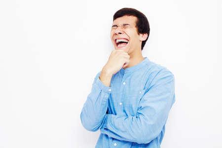 riendo: Hombre hisp�nico joven con pantalones vaqueros y gafas de pie con la mano en la barbilla y riendo en voz alta contra la pared blanca - concepto del humor Foto de archivo