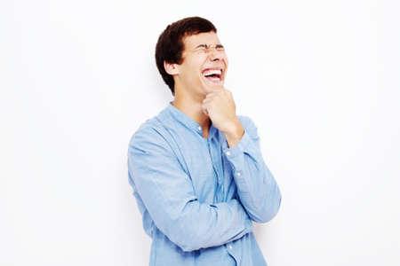 laughing out loud: Hombre hisp�nico joven con pantalones vaqueros y gafas de pie con la mano en la barbilla y riendo en voz alta contra la pared blanca - concepto del humor Foto de archivo
