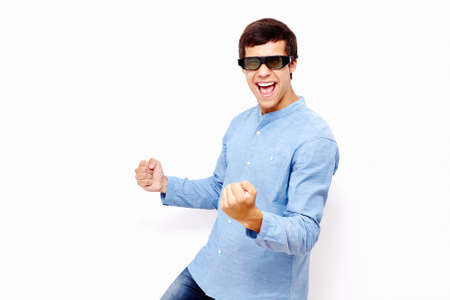 Young hispanic man wearing jeans shirt and 3D TV LCD shutter glasses laughing and celebrating win with raised fists against white wall - 3D film concept Stock Photo