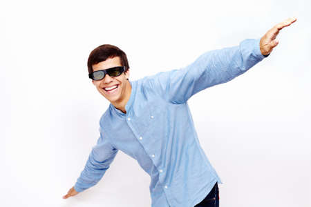 lifted hands: Young hispanic man wearing jeans shirt and 3D TV LCD shutter glasses laughing and having fun with hands outstretched lifted upwards against white wall - 3D film concept
