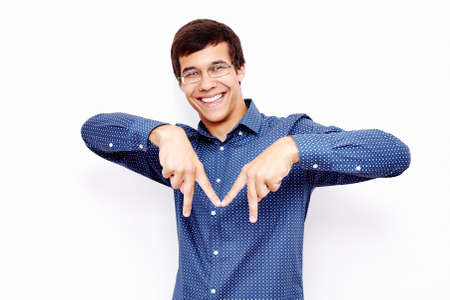 m: Young hispanic man wearing blue shirt and glasses showing M sign with his fingers and smiling against white wall - cities starting with M concept