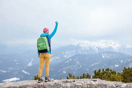 conquers: Back view of young woman wearing pink hat, blue jacket, green backpack, yellow pants and hiking boots raising her hand against winter mountains celebrating successful climb - goal concept Stock Photo